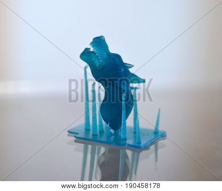 Objects photopolymer printed on a 3d printer. Muzzle of a dragon of blue color. Stereolithography 3D printer, technology of liquid photopolymerization under UV light