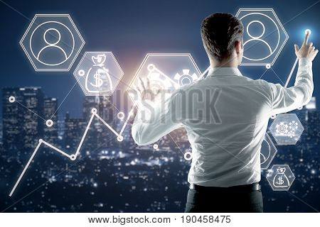 Back view of young businessman managing abstract business screen on night city background. Fund management concept