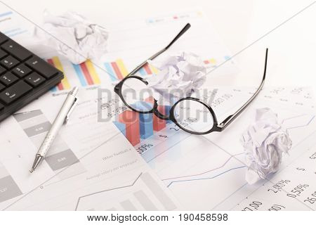 Desk with graphs keyboard glasses pen and shredded papers. Stress at work burn out