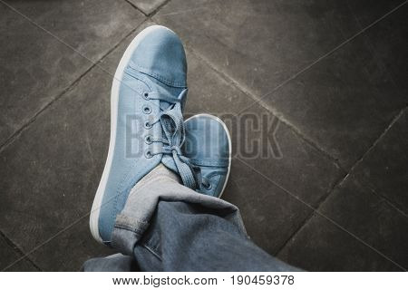 A man in jeans and blue sneakers is standing on the old floor of tiles. Top view. Close-up. Conceptual image young lifestyle. Copy spase,