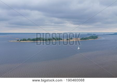 A White Sailboat In The Middle Of The River. A Lonely Sailboat.