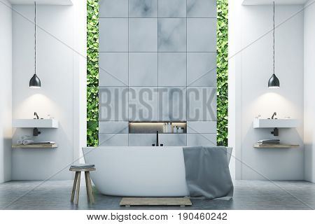 Eco bathroom interior with two narrow windows green shrubbery is seen through them. There are two sinks by the sides of a white tub standing near a marble tile wall. 3d rendering mock up