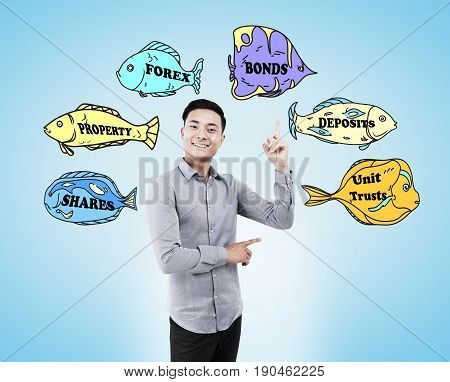 Cheerful Asian business guru is standing against a light blue background with business buzzwords written on fish of different colors.