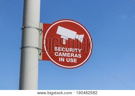 Red Security Camera In Use Sign on Gray Post and Mostly Sunny Background VI