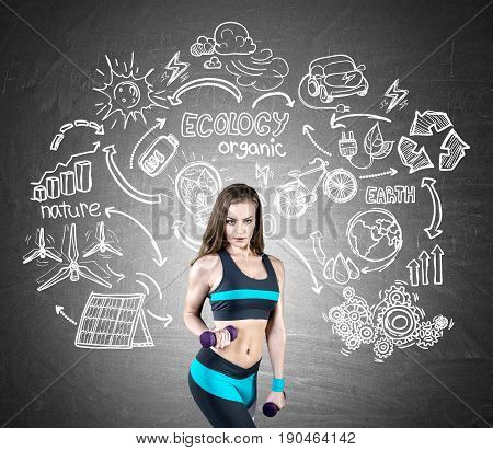Portrait of a slim young woman wearing blue and black sportswear and holding purple dumbbells. She is standing near a chalkboard with an ecology sketch on it.