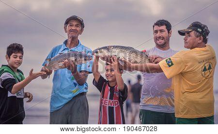 Ilha Do Mel Paraná Brazil - June 3 2017: Native fishermen from Honey Island holding fish for the photo.