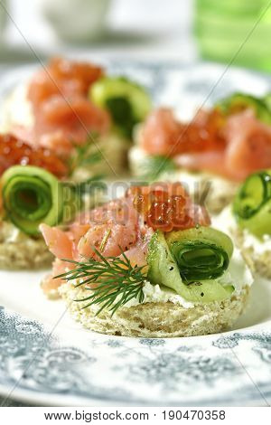 Canape With Salmon,cucumber And Red Caviar On A Curd Spread.