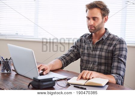 Young caucasian male writer busy digitalising his latest novel from handwritten notebook to a digital format on his modern laptop computer, while keeping place with his finger.