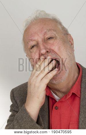 Bearded man yawning - on bright background