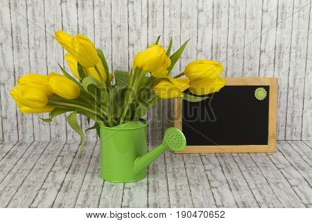 Beautiful flowers and blank blackboard on structure background