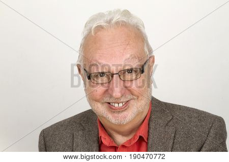 Elderly person with glasses and full beard smiling pleased - on bright background