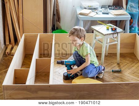 Cute young boy holding screwdriver while sitting on floor at unfinished shelf unit or bookcase