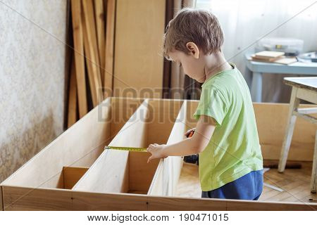 Young boy using reel to measure wooden shelf of bookcase or shelf unit