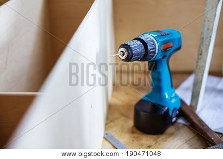 Electric screwdriver on wooden floor near unfinished shelf unit shallow depth of field