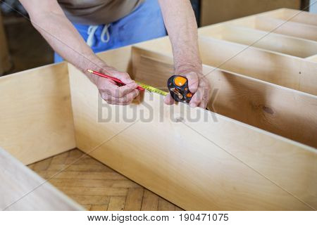 Mature man measuring wooden shelf with reel while making bookcase or shelf unit cropped view