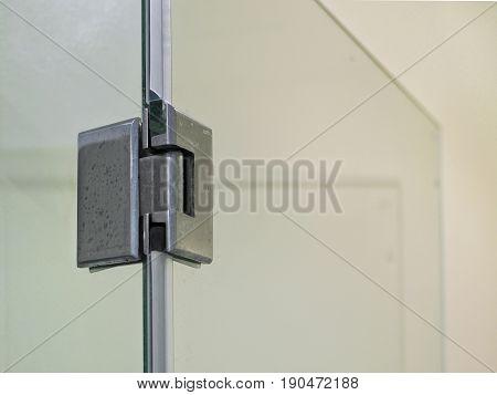 Metal Door Hinge On Glass Door In The Bathroom.