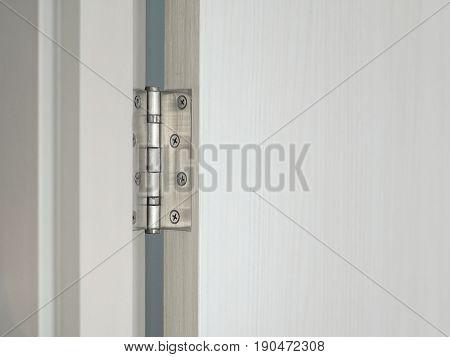 Door hinge on the white wooden door with copyspace.