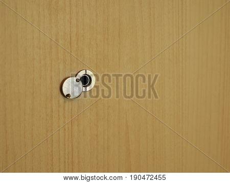 Door eye hole or peephole on wooden door.