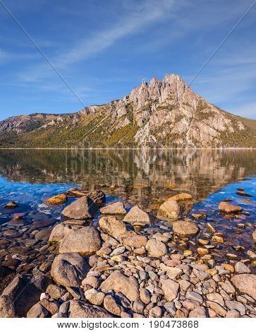 Picturesque mountain in Bariloche, Argentina. The water of shallow lake reflects sharp rocks. The concept of exotic and extreme tourism