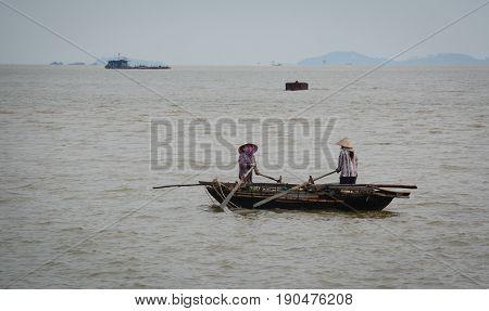 Vietnamese Women Rowing Wooden Boat
