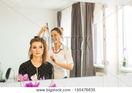 Hairdresser doing haircut for women in hairdressing salon. Concept of fashion and beauty. Positive emotion