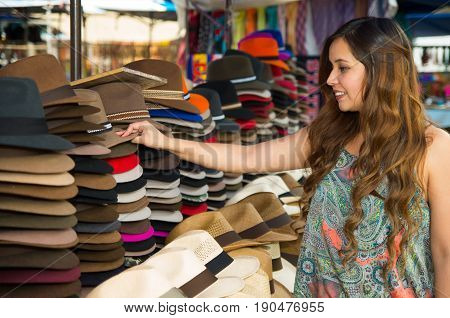 Beautiful woman touching a handmade Panama Hat at the craft market in Otavalo, Ecuador, colorful fabrics background.