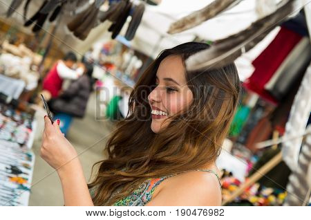 Beautiful smiling woman holding something in her hand in the andean traditional clothing and handicrafts with a blurred feather in front, market background.