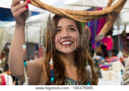 Beautiful smiling woman looking a blurred cardreams in the andean traditional clothing and handicrafts, market background.