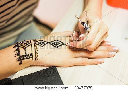 Picture of human hand being decorated with henna. mehendi hand.