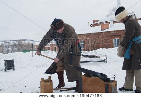 Kazan, Russia - 28 february 2017 - Sviyazhsk Island : Russian ethnic carnival Maslenitsa - A man in an old Russian military uniform charges a cast-iron gun