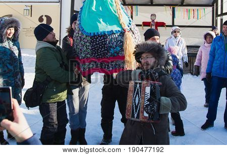 Kazan, Russia - 28 february 2017 - Sviyazhsk Island : Russian ethnic carnival Maslenitsa - A man plays the accordion in the background of a crowd of people who carry a stuffed winter