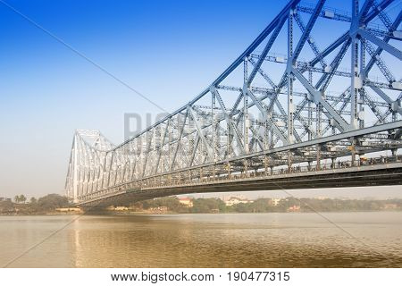 Famous Howrah Bridge connecting Howrah and Kolkata a propped cantilever bridge with a suspended span over the Hooghly River in West Bengal India. Commissioned in 1943. A busy transportation symbol of Kolkata.