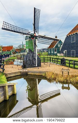 ZAANS SCHANS, NETHERLANDS - APRIL 1, 2017 Small Wooden Windmill Zaanse Schans Old Windmill Village Countryside Holland Netherlands. Working windmills from the 16th to 18th century on the River Zaan.