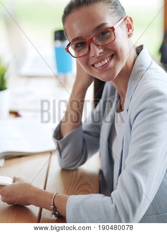 Business woman sitting in her office using a tablet computer.