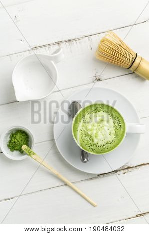 Green tea matcha latte cup top view. This latte is a delicious way to enjoy the energy boost & healthy benefits of matcha. Matcha is a powder of green tea leaves packed with antioxidants.