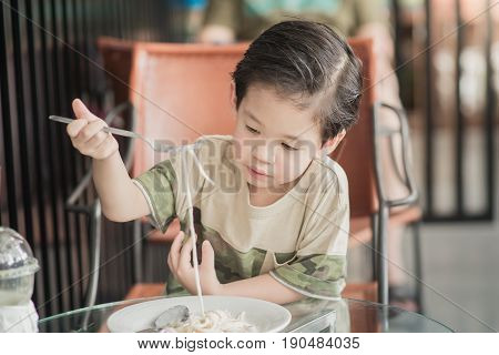Cute Asian chid eating Spaghetti Carbonara in restaurantvintage fiter