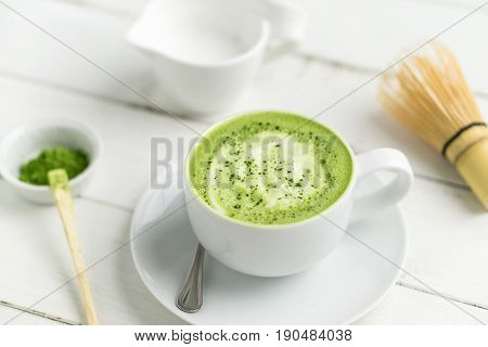 Green tea matcha latte cup with accessories. This latte is a delicious way to enjoy the energy boost & healthy benefits of matcha. Matcha is a powder of green tea leaves packed with antioxidants.