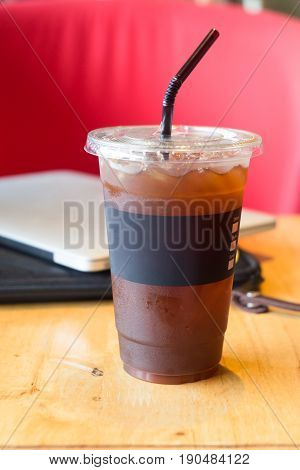 Delicious ice coffee americano with computer laptop background