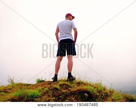 Man In Cloud Of Fog. Hiker In White Black With  Red Cap Stand On Peak .