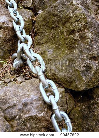 Eye Bolt With Iron Chain Anchored Into Sandstone Rock. Twisted Chain