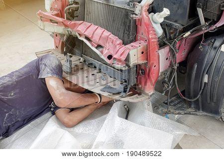 Mechanic working under car at auto service garage