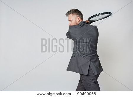 Middle aged businessman in formalwear playing tennis against grey background, copy space to the left