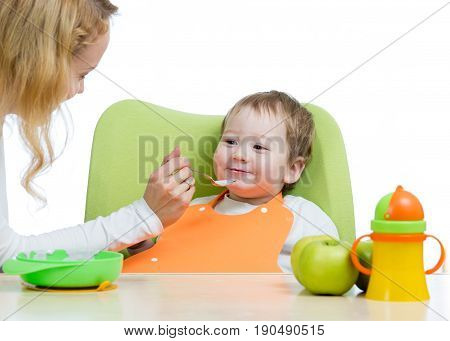 Mom feeding her kid boy with a spoon. Mother giving food to her little child. Baby food and nutrition.