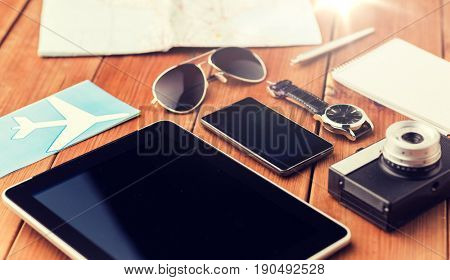 travel, tourism, technology and objects concept - close up of smartphone with tablet pc computer, airplane ticket and personal stuff