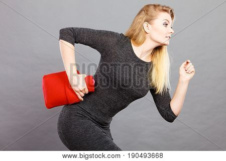 Woman holding warm red hot water bottle running somewhere in rush