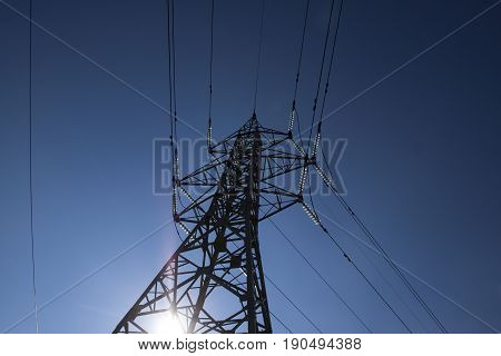 High voltage power pylons against blue sky and sun rays high-voltage power lines at sunrise.