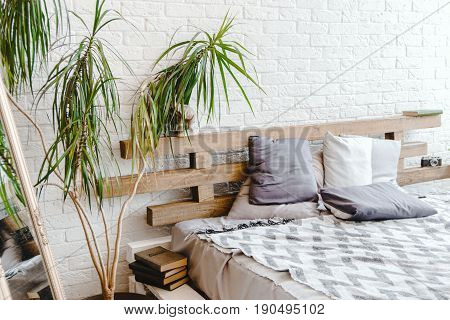 Light White Brick Interior With Mirror In The Corner, Bed And Pillows