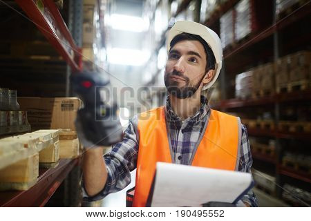 Worker with scanner standing by shelves with goods