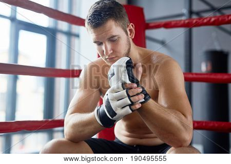 Portrait of  sweaty shirtless man sitting in boxing ring and adjusting gloves after fight