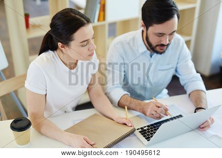 Young manager looking at laptop display and listening to co-worker explanations